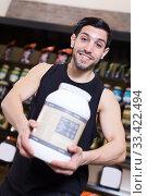 Купить «Positive muscular male seller showing sport supplements in shop», фото № 33422494, снято 28 марта 2018 г. (c) Яков Филимонов / Фотобанк Лори