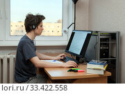 Fifteen years old boy is doing his classwork remotely from home. Стоковое фото, фотограф Юлия Кузнецова / Фотобанк Лори
