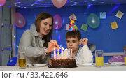 Мама с ребенком зажигают свечи на праздничном торте. Стоковое видео, видеограф Иванов Алексей / Фотобанк Лори