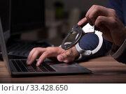 Купить «Male hacker hacking security firewall late in office», фото № 33428650, снято 15 мая 2019 г. (c) Elnur / Фотобанк Лори