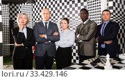 Businesspeople solving conundrum together near chessboard. Стоковое фото, фотограф Яков Филимонов / Фотобанк Лори