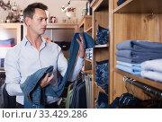 Купить «Customer examining trousers», фото № 33429286, снято 28 марта 2017 г. (c) Яков Филимонов / Фотобанк Лори