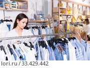 Woman customer choosing blue blouse in the fashion store. Стоковое фото, фотограф Яков Филимонов / Фотобанк Лори