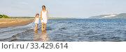 Купить «A young mother walks with her daughter on a sandy beach on a summer sunny day at sunset.», фото № 33429614, снято 18 июля 2019 г. (c) Акиньшин Владимир / Фотобанк Лори