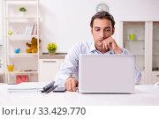 Купить «Young male businessman working at home», фото № 33429770, снято 26 июля 2019 г. (c) Elnur / Фотобанк Лори
