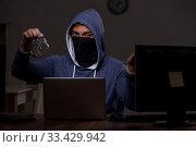 Купить «Male hacker hacking security firewall late in office», фото № 33429942, снято 15 мая 2019 г. (c) Elnur / Фотобанк Лори