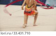 Купить «Young women giving a performance at the rhythmic gymnastics tournament using colorful ribbons», видеоролик № 33431710, снято 27 мая 2020 г. (c) Константин Шишкин / Фотобанк Лори