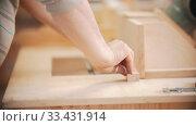 Купить «Carpentry working - hands of man worker moving the plywood to other wooden items», видеоролик № 33431914, снято 2 июня 2020 г. (c) Константин Шишкин / Фотобанк Лори