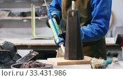 Купить «Concrete workshop - worker glueing over wooden base of pouring mold», видеоролик № 33431986, снято 3 июля 2020 г. (c) Константин Шишкин / Фотобанк Лори