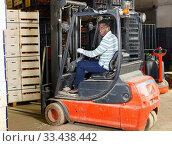 Confident African-American male forklift driver working in citrus fruit warehouse. Стоковое фото, фотограф Яков Филимонов / Фотобанк Лори
