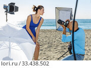 Professional photo shooting outdoors. positive female model posing to photographer on sunny beach. Стоковое фото, фотограф Яков Филимонов / Фотобанк Лори