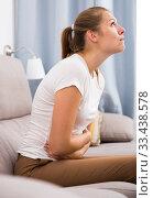 Girl is sitting unhappy because she has a stomach ache. Стоковое фото, фотограф Яков Филимонов / Фотобанк Лори