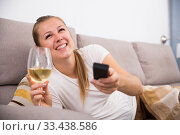 Купить «Girl is resting with wine and watching TV», фото № 33438586, снято 14 мая 2020 г. (c) Яков Филимонов / Фотобанк Лори