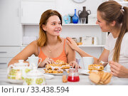 Купить «Two girlfriends are talking with tea and cake», фото № 33438594, снято 27 марта 2020 г. (c) Яков Филимонов / Фотобанк Лори