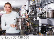 Купить «joyous woman is looking modern saucepan in the store», фото № 33438650, снято 5 февраля 2018 г. (c) Яков Филимонов / Фотобанк Лори