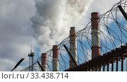Купить «Factory pipes smoke thick smoke and steam behind a fence with barbed wire», видеоролик № 33438714, снято 25 марта 2020 г. (c) Алексей Кузнецов / Фотобанк Лори