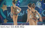 Купить «RUSSIA, KAZAN 12-03-2020, Kazan Stars Open: Young women in colorful costumes walking out from the stage of the rhythmic gymnastics tournament and holding balls», видеоролик № 33438902, снято 26 мая 2020 г. (c) Константин Шишкин / Фотобанк Лори