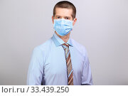 Man in light shirt, tie and medical mask looks into camera, isolated. Стоковое фото, фотограф Владимир Арсентьев / Фотобанк Лори