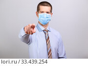 Купить «A man in a light shirt, tie and medical mask pokes his finger into a cell isolated», фото № 33439254, снято 26 марта 2020 г. (c) Владимир Арсентьев / Фотобанк Лори