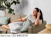 Купить «woman in headphones listening to music at home», фото № 33444614, снято 9 февраля 2020 г. (c) Syda Productions / Фотобанк Лори