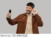 Купить «smiling young man with earphones and smartphone», фото № 33444626, снято 22 февраля 2020 г. (c) Syda Productions / Фотобанк Лори