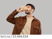 Купить «happy young man drinking coffee from takeaway cup», фото № 33444634, снято 22 февраля 2020 г. (c) Syda Productions / Фотобанк Лори