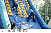 Купить «Happy friends enjoying a day at amusement park, climbing on inflatable slide with wooden poles», видеоролик № 33445170, снято 4 апреля 2020 г. (c) Яков Филимонов / Фотобанк Лори