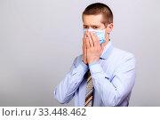 Купить «A business man in a mask grabbed his face with his hands», фото № 33448462, снято 26 марта 2020 г. (c) Владимир Арсентьев / Фотобанк Лори