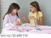 Купить «Девочка показывает другой девочке содержимое пакетика с пищевым красителем», фото № 33449114, снято 28 марта 2020 г. (c) Иванов Алексей / Фотобанк Лори