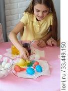 Девочка красит пасхальные яйца в специальном растворе и выкладывает на тарелку. Стоковое фото, фотограф Иванов Алексей / Фотобанк Лори