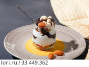 Купить «Sweet tasty milk curd creamy food in a glass jar of homemade breakfast. Cheesecake, English Trifle, Eton dessert, tiramisu, zuppa Inglese with nuts, almonds, cashews, hazelnuts, candied fruits and chocolate sauce», фото № 33449362, снято 14 декабря 2019 г. (c) Светлана Евграфова / Фотобанк Лори