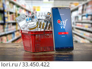 Mobile service or app for purchasing medicines in online pharmacy drugstore. Smartphone and shopping basket full of medicines. Стоковое фото, фотограф Maksym Yemelyanov / Фотобанк Лори