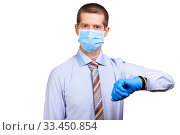 Male doctor wearing medical mask, rubber gloves, looks at watch, pointing to time. Стоковое фото, фотограф Владимир Арсентьев / Фотобанк Лори