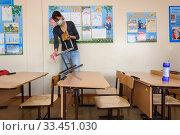 Девушка проводит генеральную уборку в школьном классе в период карантина (2020 год). Редакционное фото, фотограф Иванов Алексей / Фотобанк Лори