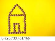 Купить «Drops of milk chocolate are laid out in a house on a yellow background», фото № 33451166, снято 14 марта 2020 г. (c) Катерина Белякина / Фотобанк Лори
