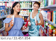 Купить «Stylish female and girl attentively looking haircare products at shop», фото № 33451854, снято 21 июня 2018 г. (c) Яков Филимонов / Фотобанк Лори