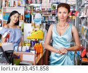 Saleswoman helping to client with payments in salon. Стоковое фото, фотограф Яков Филимонов / Фотобанк Лори