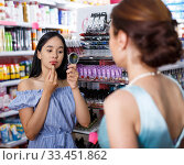 Купить «Girl shopping with mother in cosmetics store, testing new lipstick», фото № 33451862, снято 21 июня 2018 г. (c) Яков Филимонов / Фотобанк Лори