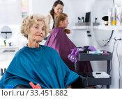 Купить «Elderly female client waiting for hair styling», фото № 33451882, снято 26 июня 2018 г. (c) Яков Филимонов / Фотобанк Лори