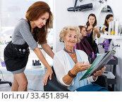 Hairdresser with senior woman choosing hairstyling in magazine. Стоковое фото, фотограф Яков Филимонов / Фотобанк Лори