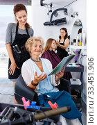 Купить «Young woman hairdresser in hair salon helping to senior woman ch», фото № 33451906, снято 26 июня 2018 г. (c) Яков Филимонов / Фотобанк Лори