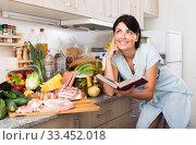 Купить «Woman searching recipe in cookbook», фото № 33452018, снято 5 сентября 2017 г. (c) Яков Филимонов / Фотобанк Лори