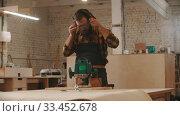Купить «Carpentry industry - man worker puts on his apron and protective glasses and starts working with a grinding machine», видеоролик № 33452678, снято 2 июня 2020 г. (c) Константин Шишкин / Фотобанк Лори