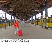 Девушка с красным чемоданом стоит на перроне железнодорожного вокзала. Гданьск, Польша (2010 год). Редакционное фото, фотограф Ирина Борсученко / Фотобанк Лори