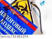 Купить «Очки , Налоговый кодекс и международный знак биологической опасности», фото № 33453014, снято 30 марта 2020 г. (c) Николай Винокуров / Фотобанк Лори