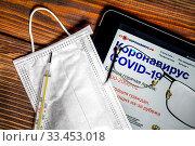 Купить «Очки, медицинская маска, градусник и планшет с открытым сайтом стопкоронавирус.рф с официальной информацией об эпидемии коронавируса COVID-19 в России», фото № 33453018, снято 30 марта 2020 г. (c) Николай Винокуров / Фотобанк Лори