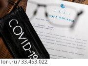 Указ Мэра города Москвы и черная медицинская маска с надписью COVID-19 лежат на столе (2020 год). Стоковое фото, фотограф Николай Винокуров / Фотобанк Лори