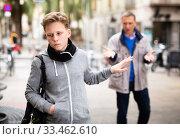 Купить «Upset teenage boy making stop gesture to dissatisfied bypasser», фото № 33462610, снято 12 июля 2020 г. (c) Яков Филимонов / Фотобанк Лори