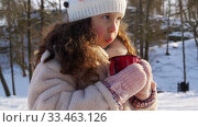 little girl with cup of hot tea in winter park. Стоковое видео, видеограф Syda Productions / Фотобанк Лори