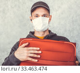Купить «Frightened tourist man in a medical mask presses with red suitcase, the concept cant leave the country, flights canceled», фото № 33463474, снято 18 марта 2020 г. (c) katalinks / Фотобанк Лори